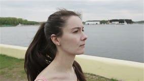 Una mujer joven con una figura delgada que comienza el funcionamiento Cámara de la cámara lenta almacen de video