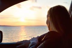 Una mujer joven considera hacia fuera la ventanilla del coche la puesta del sol en el mar Fotografía de archivo