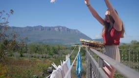 Una mujer joven cuelga hacia fuera la ropa mojada en la cuerda para secarla almacen de metraje de vídeo