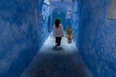 Una mujer joven da un paseo a través de las calles de Chefchaouen, la ciudad azul en Marruecos, entre las paredes y los arcos azu foto de archivo