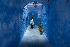 Una mujer joven da un paseo a través de las calles de Chefchaouen, la ciudad azul en Marruecos, entre las paredes y los arcos azu imagen de archivo