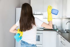 Una mujer joven de una compa??a de limpieza profesional limpia en casa Un hombre lava la cocina en guantes amarillos con imagenes de archivo