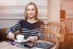 Una mujer joven de la sonrisa en el café con una taza de café que mira la cámara Chica joven con una taza de café antes de leer Fotografía de archivo libre de regalías