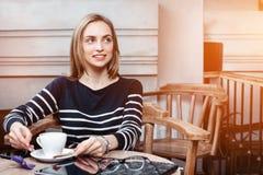 Una mujer joven de la sonrisa en el café con una taza de café que mira lejos Chica joven con una taza de café antes de leer y Fotos de archivo
