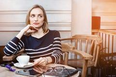 Una mujer joven de la sonrisa en el café con una taza de café que mira lejos Chica joven con una taza de café antes de leer y Foto de archivo libre de regalías