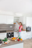 Una mujer joven de su cocina moderna Imagen de archivo libre de regalías