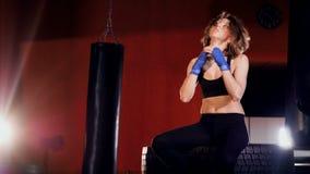 Una mujer joven del ajuste en ropa negra hace estiramientos de las puñetas en un cuarto de boxeo 4K almacen de metraje de vídeo