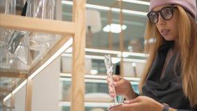 Una mujer joven del inconformista en vidrios de la moda elige los accesorios caseros en la tienda imágenes de archivo libres de regalías