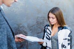 Una mujer joven del negocio entrega un documento a un hombre imagen de archivo