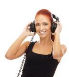 Una mujer joven del redhead que escucha la música Foto de archivo libre de regalías