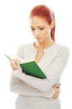 Una mujer joven del redhead que lee un libro Imágenes de archivo libres de regalías