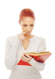 Una mujer joven del redhead que lee un libro rojo Imagen de archivo libre de regalías