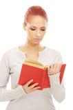 Una mujer joven del redhead que lee un libro rojo Foto de archivo libre de regalías