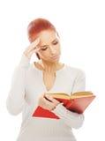 Una mujer joven del redhead que lee un libro rojo Fotos de archivo libres de regalías
