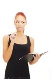 Una mujer joven del redhead que sostiene una pluma y un cuaderno Fotos de archivo