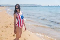 Una mujer joven delgada en una bandera de los E.E.U.U. camina a lo largo de la costa Fotos de archivo libres de regalías