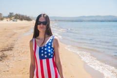 Una mujer joven delgada en una bandera de los E.E.U.U. camina a lo largo de la costa Foto de archivo libre de regalías