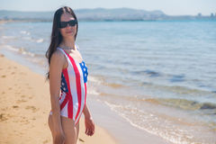 Una mujer joven delgada en una bandera de los E.E.U.U. camina a lo largo de la costa Imágenes de archivo libres de regalías