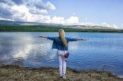 Una mujer joven delgada hermosa se coloca con su parte posterior en la orilla cerca del agua y admira el paisaje hermoso imagen de archivo libre de regalías