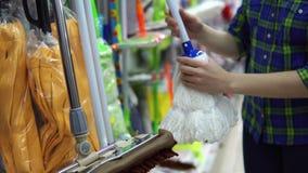 Una mujer joven elige una fregona en el supermercado metrajes