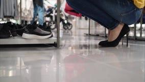 Una mujer joven elige los zapatos del ` s de los niños en una tienda Las piernas se cierran encima de la visión metrajes