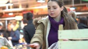 Una mujer joven elige naranjas en un supermercado metrajes