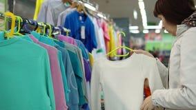 Una mujer joven elige una rebeca hecha punto para el niño en un supermercado almacen de video