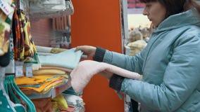 Una mujer joven elige una toalla en el supermercado almacen de metraje de vídeo