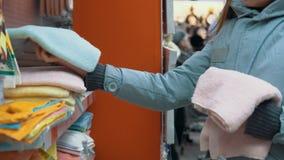 Una mujer joven elige una toalla en el supermercado almacen de video