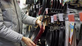 Una mujer joven elige un sartén antiadherente en la tienda