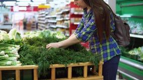 Una mujer joven elige verdes en un supermercado almacen de video