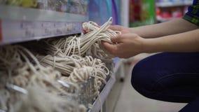 Una mujer joven elige y compra una cuerda en el supermercado almacen de video