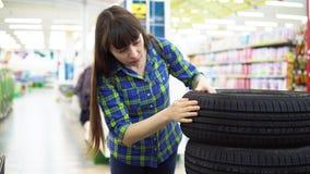 Una mujer joven elige y compra los neumáticos de coche en el supermercado almacen de video