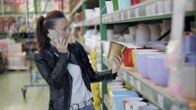 Una mujer joven elige y compra los potes plásticos coloreados para las flores Tienda de las mercancías para los floristas y los j metrajes