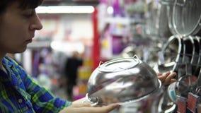Una mujer joven elige y compra un colador en el supermercado almacen de metraje de vídeo