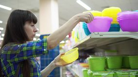 Una mujer joven elige y compra un cuenco plástico en el supermercado almacen de video