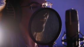 Una mujer joven emocional que registra una canción en el estudio