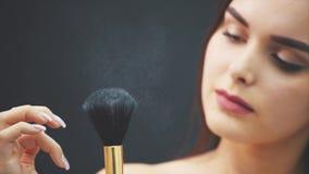 Una mujer joven empuja un cepillo con su mano La piel vuela sobre un fondo negro Imagen cosechada Uso del maquillaje adentro almacen de metraje de vídeo