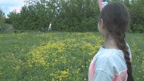 Una mujer joven en agitar gris a sus amigos a través de un campo de flor La muchacha agita a un grupo de amigos de turistas metrajes