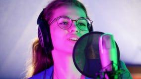 Una mujer joven en auriculares que canta en el estudio Iluminación de neón almacen de video