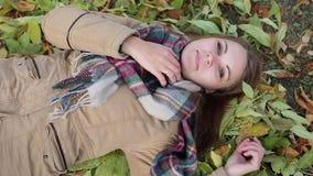 Una mujer joven en una capa que miente en las hojas de otoño Sonrisa feliz almacen de video