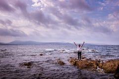 Una mujer joven en una costa tempestuosa imágenes de archivo libres de regalías