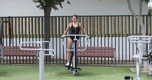 Una mujer joven en deportes traje de baño y trenes de los auriculares en un simulador en el parque almacen de video