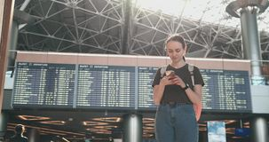 Una mujer joven en el aeropuerto con un smartphone cerca de las marcador-salidas almacen de video