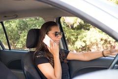 Una mujer joven en el coche habla en el teléfono elegante y conduce Foto de archivo libre de regalías