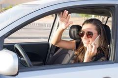 Una mujer joven en el coche habla en el teléfono elegante y conduce Foto de archivo