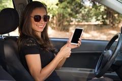 Una mujer joven en el control del carh un teléfono elegante con los pulgares para arriba Imagen de archivo libre de regalías