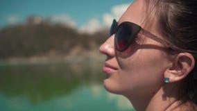 Una mujer joven en gafas de sol se sienta por el lago en un día de primavera, relajándose en naturaleza Muchacha del primer almacen de video