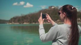 Una mujer joven en gafas de sol se sienta por el lago en un día de primavera y toma una foto en el teléfono, relajándose en natur almacen de video