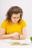 Una mujer joven en gafas está leyendo un libro Fotografía de archivo libre de regalías